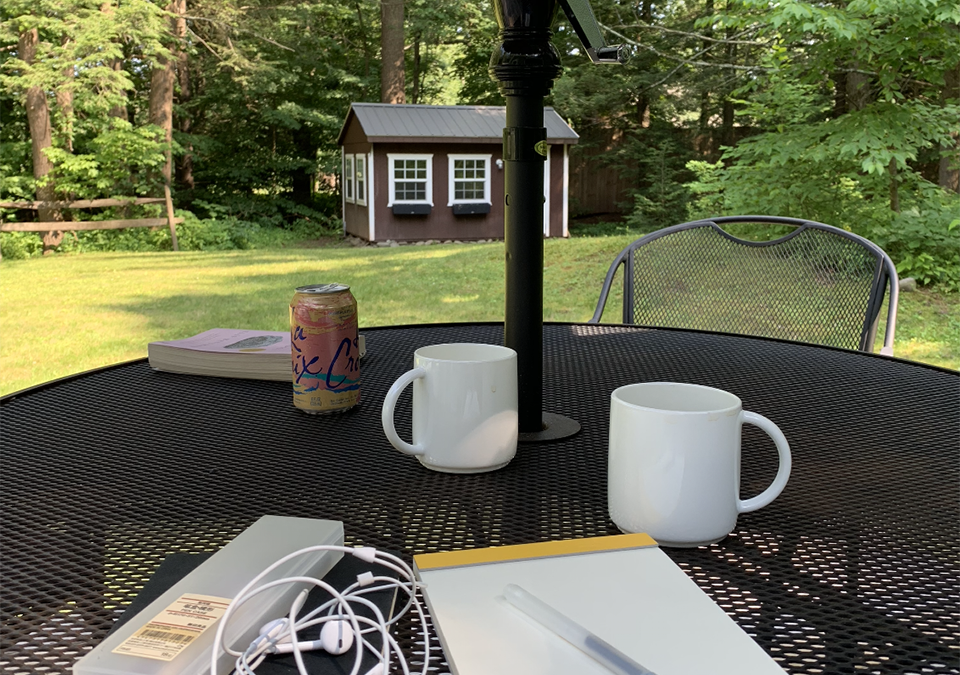 A picture of a table outdoors overlooking a yard. White mugs, a book, and a notebook sit on the table.